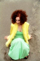 Woman with curly red hair sitting on beach