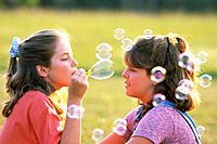 Girls blowing soap bubbles