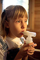 Asthmatic girl using inhaler