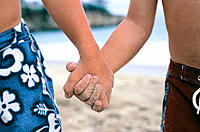 Friends holding hands at beach