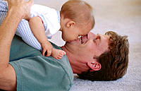 Baby kisses man on chin as they play on floor