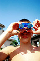 Teen boy looking through binoculars