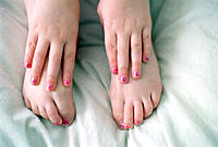 Close up of feet and hands of young girl wearing pink nail polish