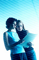 Two female office workers reading papers