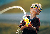 Boy wearing goggles and playing with water gun