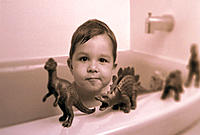 Boy in bathtub with toy dinosaurs