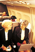 Senior Businesswomen Talking on Airplane with Laptop