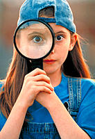 Little girl holding up magnifying glass to her eye