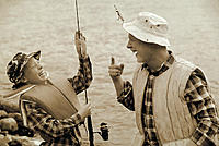 Father and son fishing, laughing as hook is caught in fathers hat