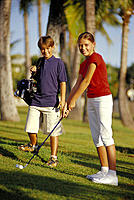 Teenage boy & girl on golf course, girl about to swing, shadows D1308