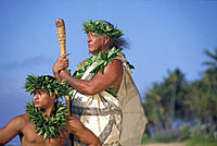 Hawaiian man in trad´l outfit w/ maile lei & haku, younger man kneel D1462