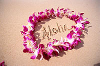HI, closeup detail of purple orchid lei on white sand, Aloha written on beach
