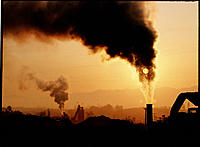Industrial air pollution. Smoke rising from achimney stack obscures the setting Sun over an asphalt plant in Canada.