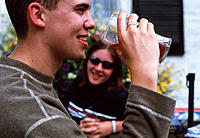 Drinking alcohol. Young man drinking from a pint of beer in a beer garden, watched by a smiling woman.