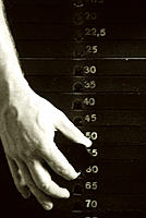 Weights. Hand adjusting the weights on a weights machine in a gymnasium.