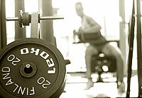 Fitness training. Rack of dumb-bell weights in front of a woman using an exercise machine in a gymnasium.