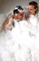Playful couple in bubble bath