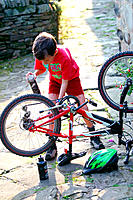 Boy lubricating his bicyle chain