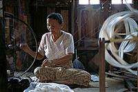 Woman spinning silk threads at factory. Myanmar