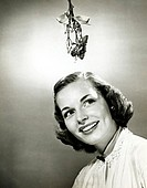Close-up of a young woman smiling with mistletoe hanging over her head