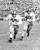 Two football players running on a football field