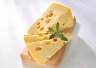 Emmental cheese in piece & in slices on wooden board
