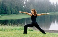 Woman performing yoga along Wark Lake. Ketchikan, Alaska. USA