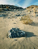 Blue rocks on sandy slope of dry lake hill, Panamint Valley. Death Valley NP. California. USA
