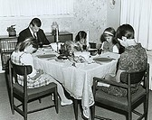 Mature couple with their three children praying at a dining table on Thanksgiving Day