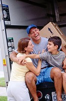 Family sitting on moving truck deck