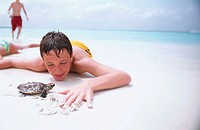 Boy (15 yrs) looking at baby Hawksbill Turtle. Maldives