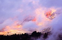 Storm clouds swirl around the upper slopes of Mount Rainier at sunrsie. Mount Rainier National Park. Washington. USA