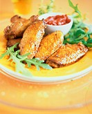 Chicken wings with salsa dip and rocket on yellow plate