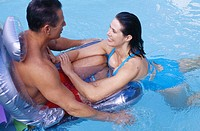 Middle aged couple in pool, man on float