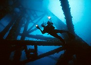 CREDIT: PETER SCOONES/SCIENCE PHOTO LIBRARY Scuba diver.  Diver  inspecting  the    submerged structure of an oil platform. Photographed off the coast...