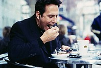 CREDIT: MICHAEL DONNE/SCIENCE PHOTO LIBRARY  Eating cake. Man eating chocolate cake at a cafe.  He is making a hands-free call on his mobile telephone...