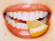 CREDIT: CRISTINA PEDRAZZINI/SCIENCE PHOTO LIBRARY Slice of lemon. Woman biting into a slice of lemon (Citrus  limon).   Lemons  are  rich in vitamin C...