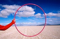 Person holding Hula hoop in desert