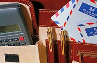 Briefcase interior with calculator, pens and stationary