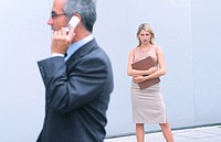 Businessman talking on cell phone, businesswoman in the background looking at camera
