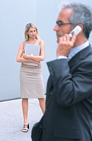 Businessman talking on cell phone, businesswoman in the background