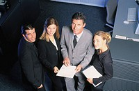 Four businesspeople with files looking at camera