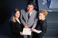 Three businesspeople with files looking at camera