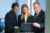 Three businesspeople looking on laptop