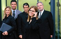 Executives looking at camera, businesswoman talking on cell phone