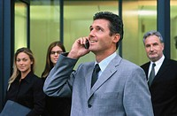 Businessman talking on cell phone, businesspeople in the background