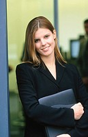 Businesswoman with files, looking at camera