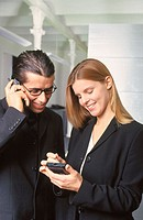 Businesswoman with personal organizer, businessman talking on cell phone