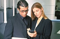 Two businesspeople looking at personal organizer