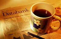 Coffee mug and newspaper